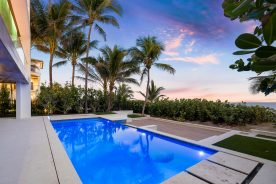 pool in front of palm trees with sun setting   2400 N. Atlantic Boulevard   florida luxurious properties